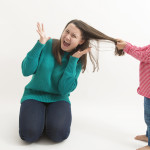 A little girl pulls her older sister hair