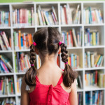 Rear view of a girl with braids in the library